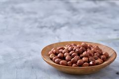 Hazelnuts in wooden plate on wihite background with copy space, top view, selective focus. Hazelnuts in wooden plate on white textured background with copy stock photos