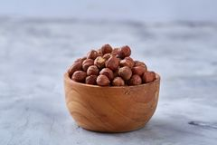 Hazelnuts in wooden plate on wihite background with copy space, top view, selective focus. Hazelnuts in wooden plate on white textured background with copy stock photography