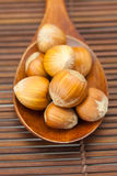 Hazelnuts on a wooden spoon on a bamboo mat Royalty Free Stock Photography