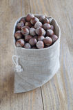 Hazelnuts on a wooden table. Hazelnuts in a cotton bag on a wooden table Stock Photography