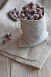 Hazelnuts on a wooden table. Hazelnuts in a cotton bag on a wooden table Royalty Free Stock Photography