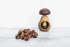 Hazelnuts on wooden table with one nut in mushroom-shaped nut-cracker Royalty Free Stock Photo