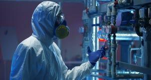hazmat衣服的科学家检查测量仪的 股票录像