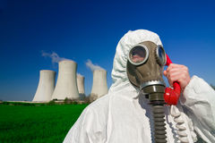 Hazmat man at nuclear station. A view of a man wearing a breathing mask and a hazmat suit, standing in front of a nuclear power station and talking on a red stock image