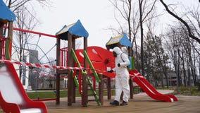 Hazmat team disinfects playground surfaces on coronavirus covid-19 quarantine with antibacterial sanitizer sprayer