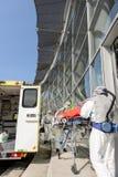 HAZMAT-team met brancard door ziekenwagen stock afbeeldingen
