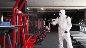 Hazmat worker disinfects gym fitness equipment from coronavirus covid-19 hazard with antibacterial sanitizer sprayer on