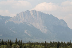 Hazy behemoth. A mountain is visible in Kananaskis country through the haze of smoke from forest fires Stock Photos