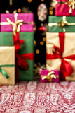Hazy Christmas Background. Christmas presents piled-up on a festive cloth. Wrapping and ribbons in gold, red, magenta and green. Twinkles and blurred stars in Stock Image