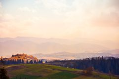 Hazy evening in mountain. S. lovely countryside in autumn. warm weather with pinkish clouds on the sky royalty free stock images