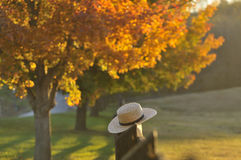 Hazy Fall Evening in Lancaster Pennsylvania. Amish straw hat laying over farm fence post on hazy fall evening in Pennsylvania Stock Photo