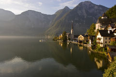 Hazy morning on a lake. Boat sailing into the morning fog over a lake in Hallstatt, Austria Royalty Free Stock Images