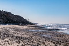 Hazy Morning at South Carlsbad State Beach. A hazy morning at South Carlsbad State Beach in San Diego, California, a beach covered by stones stock photo