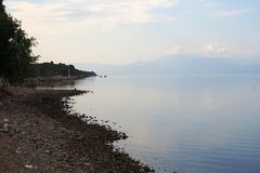 Hazy and Overcast Seascape, Gulf of Corinth, Greece. A hazy and overcast day on the Corinthian Gulf, with pale sky reflected in the calm sea water, and Stock Image