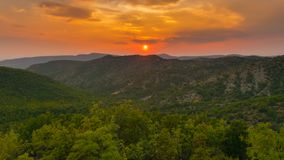Hazy red sunset over a green forest. A hazy sunset hanging over a vast mountains covered in green forest stock photography