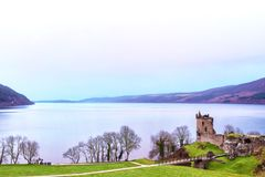 Hazy Skies over a Castle and Loch Ness in Scotland stock photography