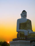 Hazy Sunset by Buddha Statue. Burma (Myanmar). Seated Buddha Statue, approx 6 meter tall, with sunet burning through low haze. Picture taken near Namsaw, Shan royalty free stock image