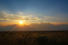 Hazy sunset at Grand Tetons National Park. Sun setting behind the Teton Range in Wyoming Stock Photos