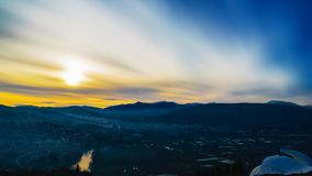 Hazy Sunset Over a Cityscape. A long exposure of a sunset over a small, hazy town stock photos