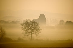 Hazy winter morning with landscape and a church stock photography