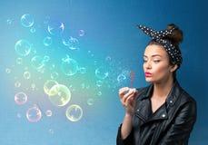 Hübsche Dame, die bunte Blasen auf blauem Hintergrund durchbrennt Stockfotografie