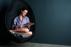Hübsche Frau auf Blasenstuhl-Lesezeitschrift Lizenzfreies Stockbild