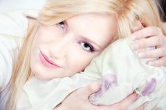 Hübsche Frau auf Kissen Stockbild