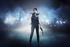 Hübsche Frau in der Polizeiweste, die Baseballschläger hält Stockfotos
