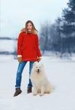 Hübsche Frau in der roten Jacke gehend mit weißem Samoyedhund Lizenzfreie Stockfotografie