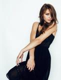 Hübsche Frau des jungen Brunette im schwarzen Kleid, das auf weißem Hintergrund mit aufwirft, bilden sexy Lizenzfreies Stockbild