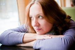 Hübsche Frau, die auf einer Tabelle sich lehnt Lizenzfreie Stockfotografie