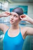 Hübsche Frau, die auf Schwimmenkappe sich setzt Stockbild