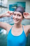 Hübsche Frau, die auf Schwimmenkappe sich setzt Lizenzfreies Stockbild