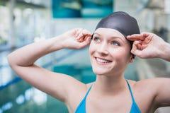 Hübsche Frau, die auf Schwimmenkappe sich setzt Lizenzfreies Stockfoto