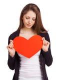 Hübsche Frau, die ein rotes Herz hält Stockbild