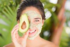 Hübsche Frau, die eine Avocado zeigt Stockfotos