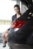 Hübsche Frau, die in einem Autokofferraum sitzt Lizenzfreies Stockfoto