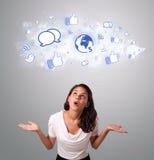 Hübsche Frau, die Ikonen des Sozialen Netzes in der abstrakten Wolke schaut Lizenzfreies Stockfoto