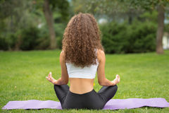 Hübsche Frau, die Yogasitzt Meditation zurück, tuend Stockfotos