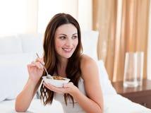 Hübsche Frau, welche die Getreide sitzen auf Bett isst Lizenzfreie Stockbilder