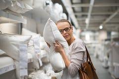 Hübsche, junge Frau, die das rechte Kissen wählt Lizenzfreies Stockfoto