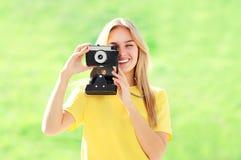 Hübsche lächelnde Blondine des Porträts mit Retro- Kamera Stockbild