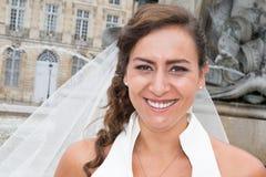 Hübsche lächelnde Braut, die einen Schleier in der Stadt trägt Stockfotografie