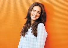 Hübsche lächelnde Frau des Lebensstilporträts, die gegen buntes aufwirft Stockbilder