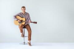 Hübsche lächelnde Gitarristspielmusik, die auf Stuhl stationiert Stockbild