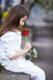 Hübsche Mädchengeruchrose im Freien in der weißen Klage Lizenzfreie Stockfotos
