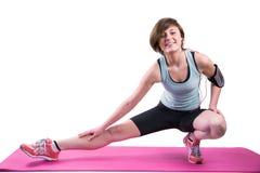 Hübscher Brunette, der Kamera betrachtet und ihr Bein auf Übungsmatte ausdehnt Lizenzfreies Stockbild