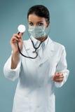 Hübscher Doktor, der mit Stethoskop überprüft Stockbilder