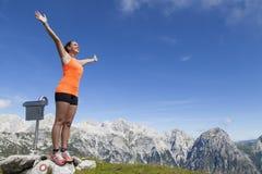 Hübscher Frauenwanderer, der auf einem Felsen mit den angehobenen Händen steht Lizenzfreie Stockfotografie