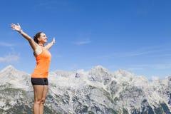 Hübscher Frauenwanderer, der auf einem Felsen mit den angehobenen Händen steht Stockbilder
